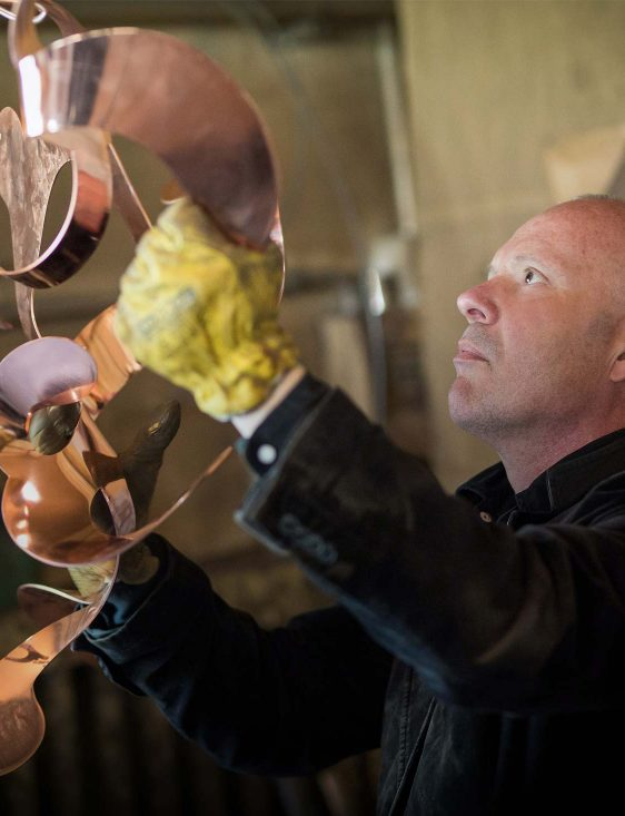 william brand working on a contemporary chandelier from his modern lighting collections
